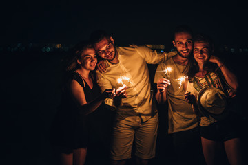 Group of people is holding sparkle sticks while enjoying on the beach by night, low key, dark image