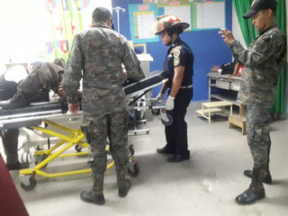 A firefighter helps injured soldier in Izabal, as Guatemala declares a state of siege after the murder of three marines