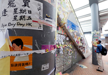A man takes a picture of posters and sticker notes supporting the anti-government protest movement near the Central Government Offices in Hong Kong