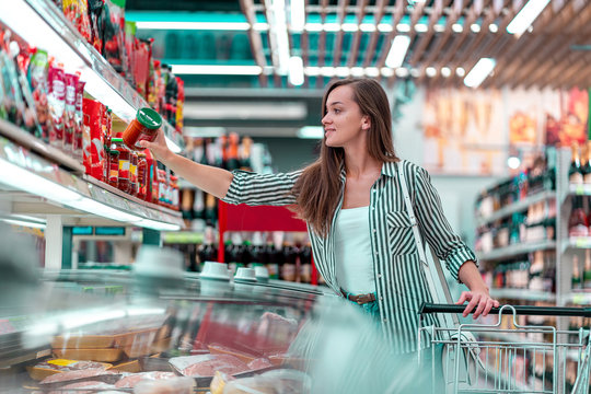 Young woman with shopping cart chooses and buying products at the grocery store. Buying food at supermarket