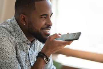 Close up happy black man dictating voice message.