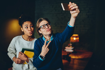 Young multiracial colleagues posing for common selfie on smartphone camera during free time indoors, male and female hipsters making funny faces while taking picture on modern cellular for share .