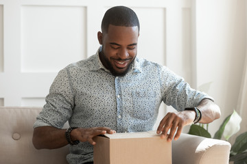 Happy young african american man unboxing delivery parcel.