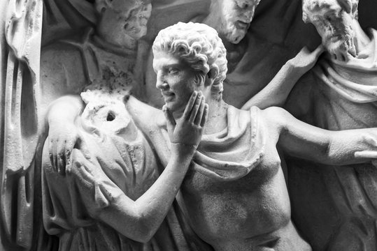 Black and white photo of marble sculptures showing a man hugging a headless female statue