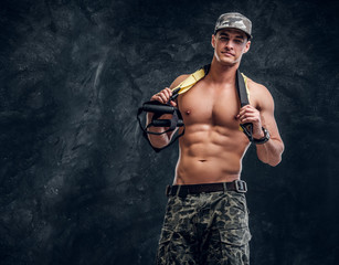 Muscular shirtless man in cap is doing exercises with gum over dark background.
