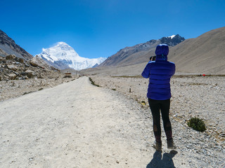CLOSE UP: Unrecognizable woman takes photos of windswept Everest from Base Camp.
