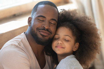Close up head shot young black man embracing little daughter.