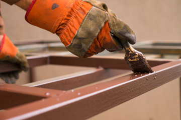 Contractor's hand with brush that painting metal construction.
