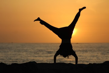 Silhouette of a female doing a cartwheel with a blurred sea and a clear sky in the background