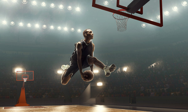 African american basketball player in action on a floodlit court. Slam dunk