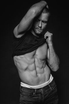 Black and White Muscle strong beautiful stripped male model with black t-shirt in denim blue jeans on black isolated font background