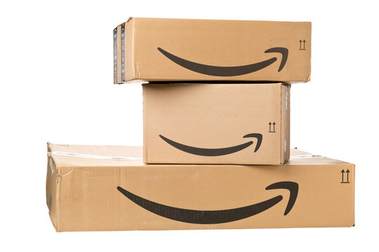 DRESDEN, GERMANY - APRIL 3, 2019 : Amazon logo on stack of delivered parcels isolated on white background
