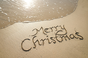 Merry Christmas message handwritten in smooth sand with an oncoming wave on the shore of a tropical beach