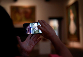 A woman uses her cell phone to take pictures of paintings during the presentation of the exhibition of paintings of Mexican muralist Diego Rivera and Mexican artist Frida Kahlo in Mexico City