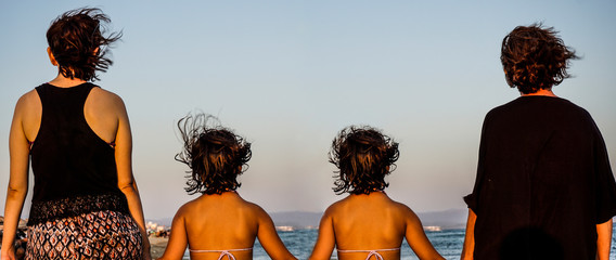 Grandmother, mother and daughter twins walking on sand. Three different generation conceptual picture.