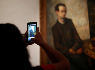 "A woman uses her cell phone to take a picture of painting ""The Mathematician"" 1918 by Diego Rivera during the presentation of the exhibition of Mexican muralist Diego Rivera and Mexican artist Frida Kahlo, in Mexico City"