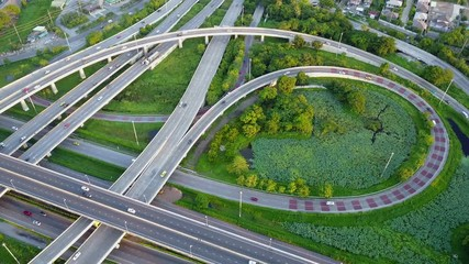 Fotobehang - 4K. Aerial view of road interchange or highway intersection with busy urban traffic speeding on the road. Junction network of transportation taken by drone.