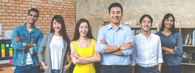 Banner of Group asian employee are standing and looking at camera with feeling confident at workplace company. Portait of Asian creative team posing in workspace.