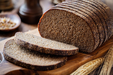 Sliced rye bread on a rustic cutting board with grain and rye ears at the background