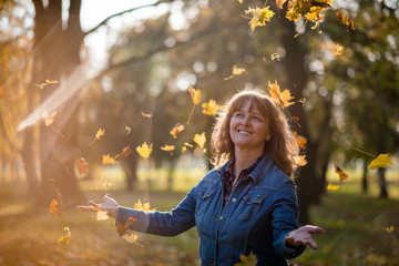 Woman enjoying autumn - leaves in the air