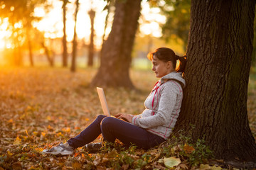 Woman working on laptop under the tree in park
