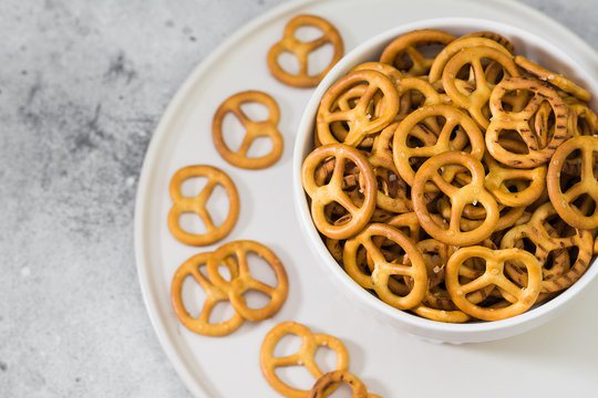 Pretzels in a white vase on a light gray background
