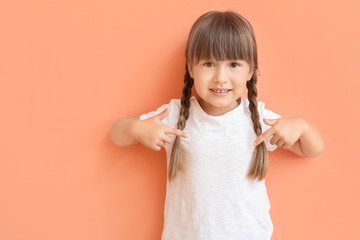 Little girl pointing at her t-shirt on color background