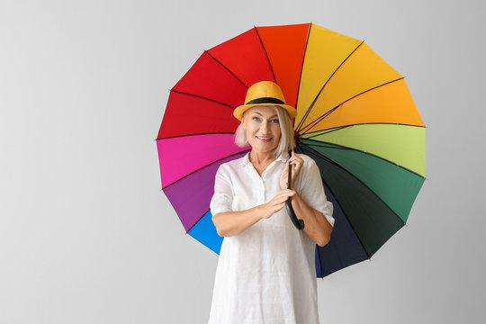 Stylish mature woman with umbrella on light background
