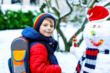 Little school kid boy in colorful clothes, with glasses and backpack having fun with snowman after elementary school end