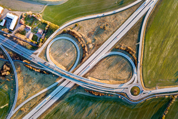 Aerial top view of modern highway road intersection, house roofs on spring green field background....