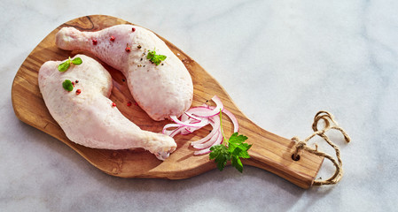 Two raw chicken drumsticks with thighs