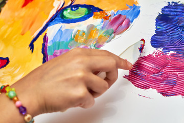 A girl paints a colorful lion on canvas using a brush and knife. Closeup, selective focus
