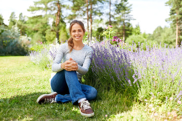 gardening and people concept - happy young woman sitting on grass near lavender flowers on summer garden bed