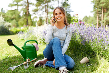 gardening, technology and people concept - happy young woman or gardener with garden tools calling...