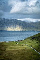 Dramatic landscape of Faroe Islands with remote road in a middle of mountains.
