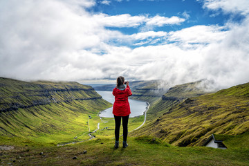 Female traveler standing at top of mountain and taking photos of spectacular view over Faroe Islands fjords.