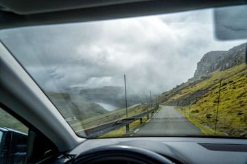 Driver's perspective from the inside of a car during a road trip through snow-covered valleys on the Faroe Islands.