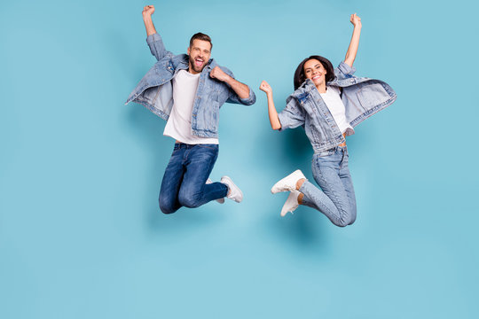 Photo of overjoyed joyful cute nice couple of spouses jumping flying in air happily while isolated with blue background