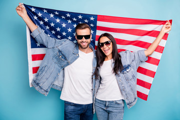 Portrait of cheerful married people in eyewear eyeglasses holding us flag screaming wearing denim jeans jacket isolated over blue background Wall mural