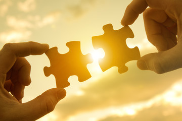Two hands connect pieces of the puzzle against the sunset. Business concept idea, promotion,...