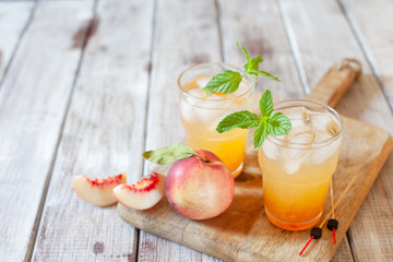 Peach cocktail with mint on white wooden background