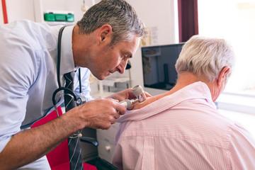 Male dermatologist examining senior patient with dermatoscopy