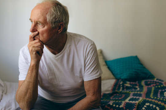 Senior male patient sitting on bed at retirement home