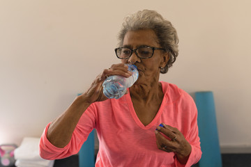 Senior woman drinking water after workout