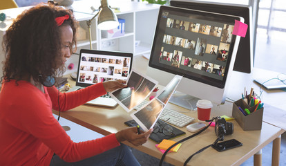 Female graphic designer looking photographs at desk