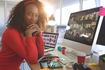 Female graphic designer with hands on chin looking at camera while sitting at desk