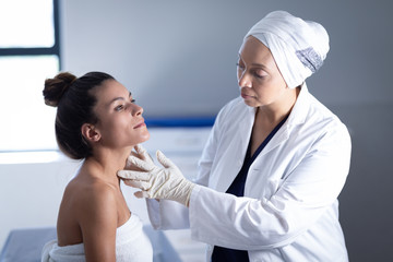 Mature female doctor checking neck of woman in clinic