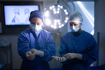 Female surgeons wearing latex gloves before operation