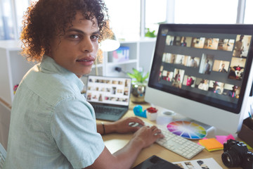 Male graphic designer looking at camera while working