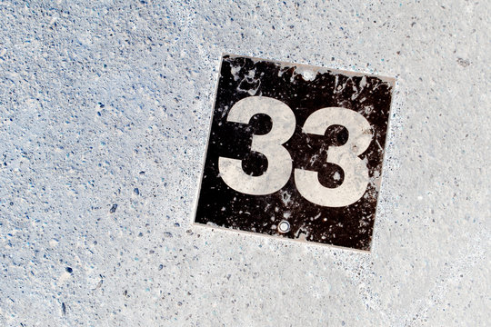 Number 33 black plate on white wall background